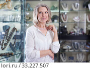 Adult woman trying on a rose quartz necklace and earrings at a jewelry store. Стоковое фото, фотограф Яков Филимонов / Фотобанк Лори