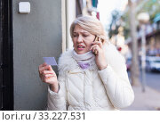 Adult female is talking by phone about her note on the street. Стоковое фото, фотограф Яков Филимонов / Фотобанк Лори