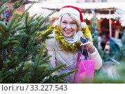 Woman is preparing for Christmas and choosing X-mas tree. Стоковое фото, фотограф Яков Филимонов / Фотобанк Лори
