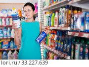 Купить «Woman choosing detergent for washing», фото № 33227639, снято 6 июня 2017 г. (c) Яков Филимонов / Фотобанк Лори
