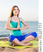 Купить «Female 20-25 years old is sitting and practicing meditation in blue T-shirt», фото № 33227711, снято 4 августа 2017 г. (c) Яков Филимонов / Фотобанк Лори