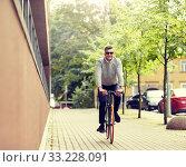Купить «young man riding bicycle on city street», фото № 33228091, снято 21 августа 2016 г. (c) Syda Productions / Фотобанк Лори