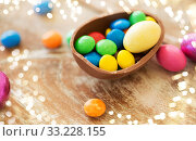 chocolate easter egg and candy drops on table. Стоковое фото, фотограф Syda Productions / Фотобанк Лори