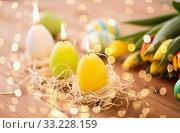 Купить «candles in shape of easter eggs and tulip flowers», фото № 33228159, снято 15 марта 2018 г. (c) Syda Productions / Фотобанк Лори