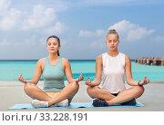 Купить «women doing yoga and meditating in lotus pose», фото № 33228191, снято 28 июля 2019 г. (c) Syda Productions / Фотобанк Лори