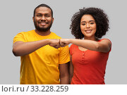 Купить «african american couple making fist bump gesture», фото № 33228259, снято 15 декабря 2019 г. (c) Syda Productions / Фотобанк Лори