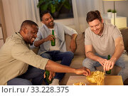 male friends drinking beer with crisps at home. Стоковое фото, фотограф Syda Productions / Фотобанк Лори