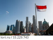 Singapore, Republic of Singapore, state flag in front of city view with skyscrapers in the business district (2020 год). Стоковое фото, агентство Caro Photoagency / Фотобанк Лори