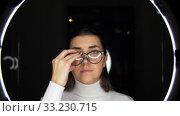Купить «woman in glasses over white illumination on black», видеоролик № 33230715, снято 23 декабря 2019 г. (c) Syda Productions / Фотобанк Лори