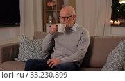 Купить «happy senior man drinking tea at home in evening», видеоролик № 33230899, снято 4 января 2020 г. (c) Syda Productions / Фотобанк Лори