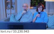 happy senior couple drink red wine and watch tv. Стоковое видео, видеограф Syda Productions / Фотобанк Лори