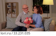 happy senior couple with bunch of flowers at home. Стоковое видео, видеограф Syda Productions / Фотобанк Лори