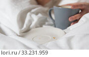 hand of woman eating croissant with coffee in bed. Стоковое видео, видеограф Syda Productions / Фотобанк Лори