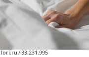 Купить «hand of woman squeezing white bed linen or blanket», видеоролик № 33231995, снято 22 января 2020 г. (c) Syda Productions / Фотобанк Лори