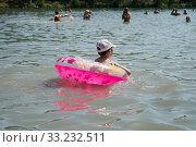Купить «Маленькая девочка плавает в озере с надувным кругом на фоне купающихся людей», фото № 33232511, снято 3 августа 2019 г. (c) Светлана Попова / Фотобанк Лори