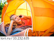 Купить «Pretty, young woman camping outdoors, lying in the tent in the morning, using her smart phone», фото № 33232635, снято 10 июля 2020 г. (c) PantherMedia / Фотобанк Лори