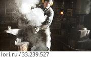 Купить «Blacksmith cooling out hot detail in the bucket of cool water», видеоролик № 33239527, снято 7 апреля 2020 г. (c) Константин Шишкин / Фотобанк Лори