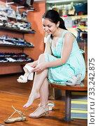 Купить «Girl is trying on heeled sandals in shoes shop», фото № 33242875, снято 10 мая 2017 г. (c) Яков Филимонов / Фотобанк Лори