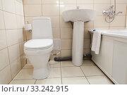 Купить «Interior of simple half bathroom with toilet, sink and bath with shower, white sanitary ware», фото № 33242915, снято 6 июля 2015 г. (c) Кекяляйнен Андрей / Фотобанк Лори