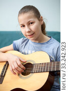 Teenager girl slams on her acoustic guitar, looking at camera. Стоковое фото, фотограф Кекяляйнен Андрей / Фотобанк Лори