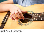 Купить «Female hand plucks the strings of a yellow acoustic guitar, close up view», фото № 33242927, снято 7 февраля 2020 г. (c) Кекяляйнен Андрей / Фотобанк Лори