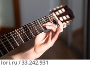 Купить «Close up view at acoustic guitar fretboard with female hand striking a chord», фото № 33242931, снято 7 февраля 2020 г. (c) Кекяляйнен Андрей / Фотобанк Лори