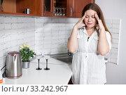 Купить «Stressed woman touching her head, standing in domestic kitchen with headache. Everyday routine duties of housewife», фото № 33242967, снято 27 июля 2015 г. (c) Кекяляйнен Андрей / Фотобанк Лори