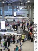Crowd of passengers stand in baggage claim area in the Pulkovo International Airport. It is new modern terminal for arriving people in city (2015 год). Редакционное фото, фотограф Кекяляйнен Андрей / Фотобанк Лори