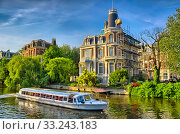 Boat on Amstel river near beautiful houses in Amsterdam, Holland. Стоковое фото, фотограф Dmitry Orlov / PantherMedia / Фотобанк Лори