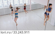 Young women spinning on the poles in bright studio with big mirrors. Стоковое фото, фотограф Константин Шишкин / Фотобанк Лори