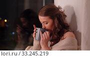 Купить «young woman drinking coffee or tea at window», видеоролик № 33245219, снято 21 января 2020 г. (c) Syda Productions / Фотобанк Лори