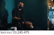 Купить «Man barber in black mask with tattoes washing his client hair», видеоролик № 33245475, снято 30 марта 2020 г. (c) Константин Шишкин / Фотобанк Лори