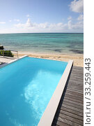 Beautiful view of infinity pool with wooden deck. Стоковое фото, фотограф Fabrice Michaudeau / PantherMedia / Фотобанк Лори