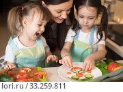 Cute mom and her kids making funny face from vegetables. Стоковое фото, фотограф Оксана Кузьмина / Фотобанк Лори