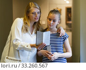 Купить «Young woman visitor with daughter with guide book looking at exhibition», фото № 33260567, снято 21 октября 2018 г. (c) Яков Филимонов / Фотобанк Лори