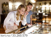 Woman visitor with daughter looking to art objects under glass with guide book. Стоковое фото, фотограф Яков Филимонов / Фотобанк Лори