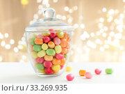 Купить «glass jar with candy drops over lights background», фото № 33269935, снято 6 июля 2018 г. (c) Syda Productions / Фотобанк Лори