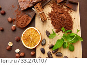 Купить «chocolate with hazelnuts, cocoa beans and powder», фото № 33270107, снято 1 февраля 2019 г. (c) Syda Productions / Фотобанк Лори