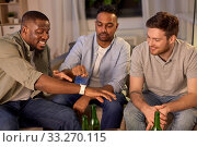 Купить «male friends with smart watch and beer at home», фото № 33270115, снято 28 декабря 2019 г. (c) Syda Productions / Фотобанк Лори