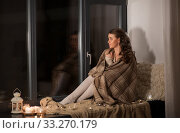 woman in blanket sitting on windowsill at home. Стоковое фото, фотограф Syda Productions / Фотобанк Лори