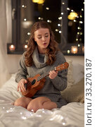 Купить «happy young woman playing guitar in bed at home», фото № 33270187, снято 19 января 2020 г. (c) Syda Productions / Фотобанк Лори