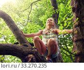 Купить «happy girl climbing up tree in summer park», фото № 33270235, снято 24 июля 2016 г. (c) Syda Productions / Фотобанк Лори