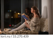 woman reading book sitting on windowsill at home. Стоковое фото, фотограф Syda Productions / Фотобанк Лори