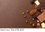 Купить «chocolate with nuts, cocoa beans and powder», фото № 33270631, снято 1 февраля 2019 г. (c) Syda Productions / Фотобанк Лори