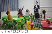 Купить «Portrait of happy diligent schoolchildren sitting with hands raised during lesson with female teacher in classroom», видеоролик № 33271403, снято 29 января 2020 г. (c) Яков Филимонов / Фотобанк Лори