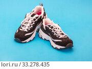 Купить «Чёрно-белые спортивные кроссовки на голубом фоне», фото № 33278435, снято 26 января 2020 г. (c) V.Ivantsov / Фотобанк Лори