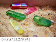Multicolored crystal quartz sticks made of gems lie on the sand. Стоковое фото, фотограф Федонников Никита Александрович / Фотобанк Лори