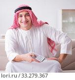 Купить «Young arab man watching tv sitting on the sofa», фото № 33279367, снято 12 декабря 2016 г. (c) Elnur / Фотобанк Лори