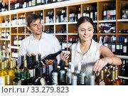 Happy young couple choosing together wine. Стоковое фото, фотограф Яков Филимонов / Фотобанк Лори