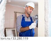 Man in helmet is sawing wall with circular saw. Стоковое фото, фотограф Яков Филимонов / Фотобанк Лори